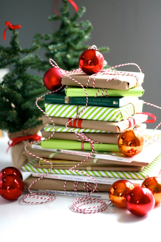 Books wrapped in holiday paper with Christmas ornaments and fake green little trees in the background.